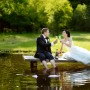 Bride and groom drinking champagne by the lake.